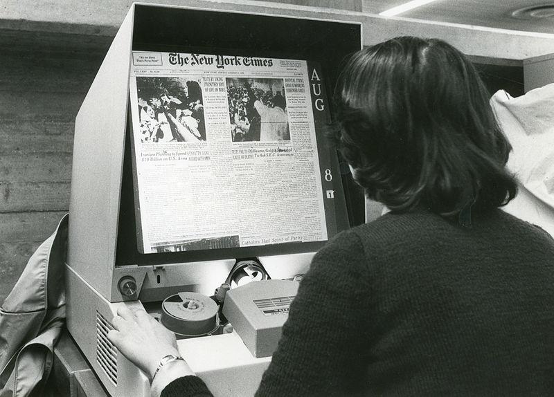 Woman using microfilm reader